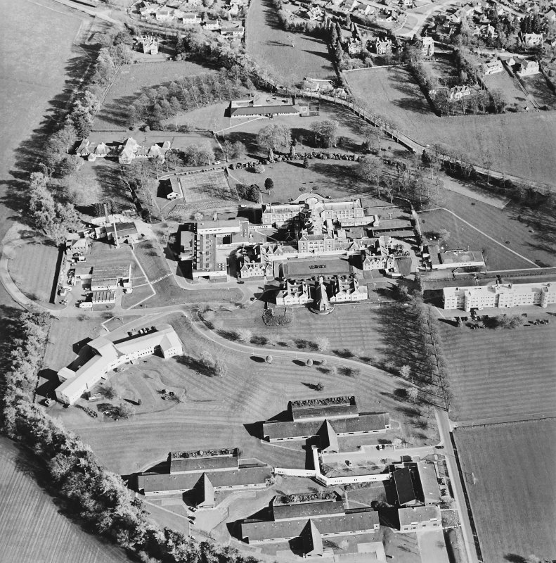 Oblique aerial view centred on the hospital and chapel, taken from the NW.