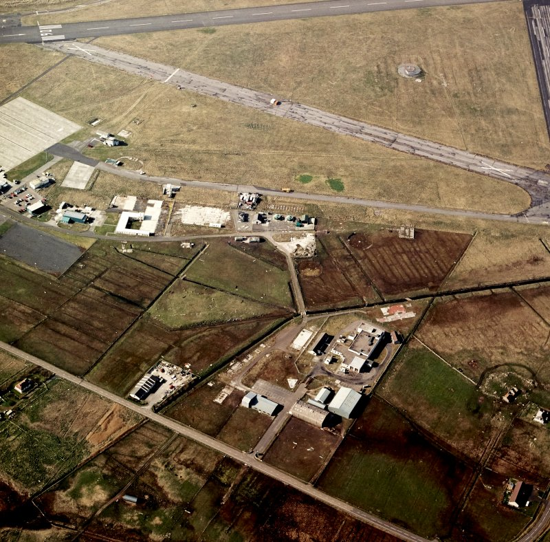 Oblique aerial view centred on the village with the airfield adjacent, taken from the SSE.