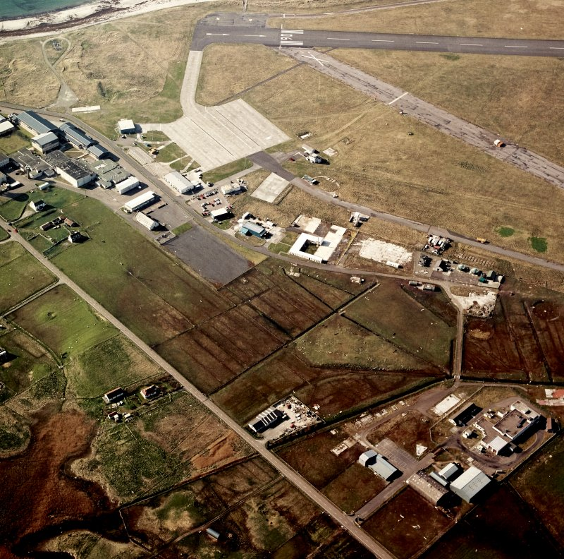 Oblique aerial view centred on the village with the airfield adjacent, taken from the SE.