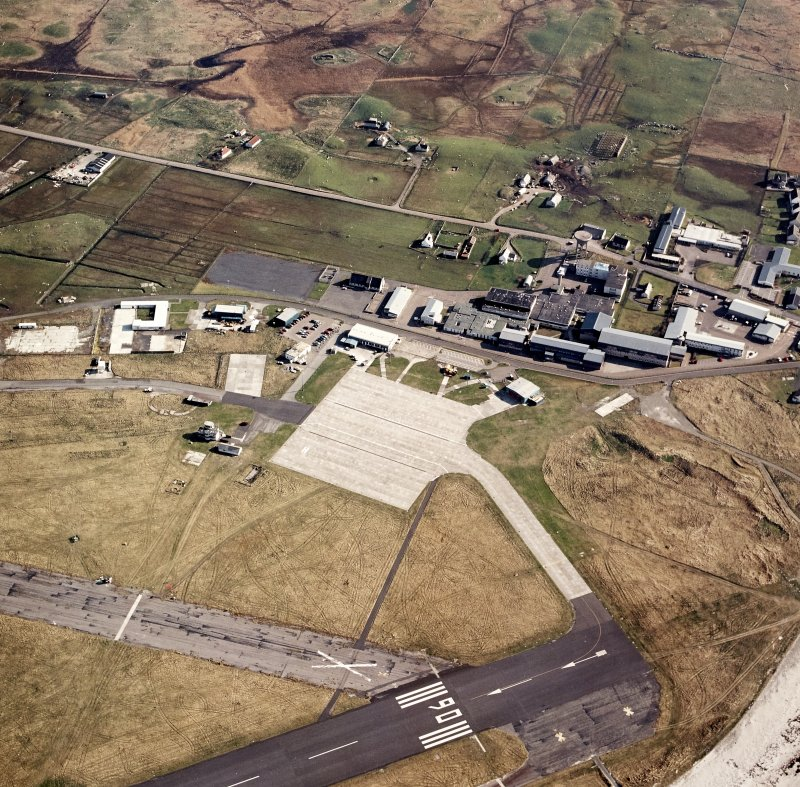 Oblique aerial view centred on the village with the airfield adjacent, taken from the N.