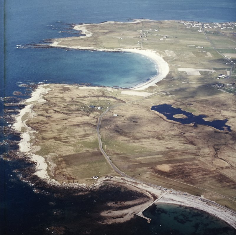 General oblique aerial view looking across the jetty towards the township of Balvanich and the crofting township of Aird, with the remains of the dun adjacent, taken from the SSW.