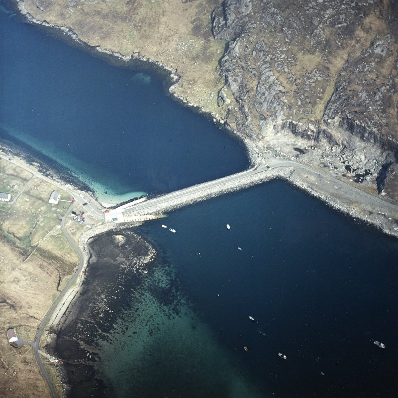 Oblique aerial view centred on the causeway and slipways with the quarry adjacent, taken from the SE.