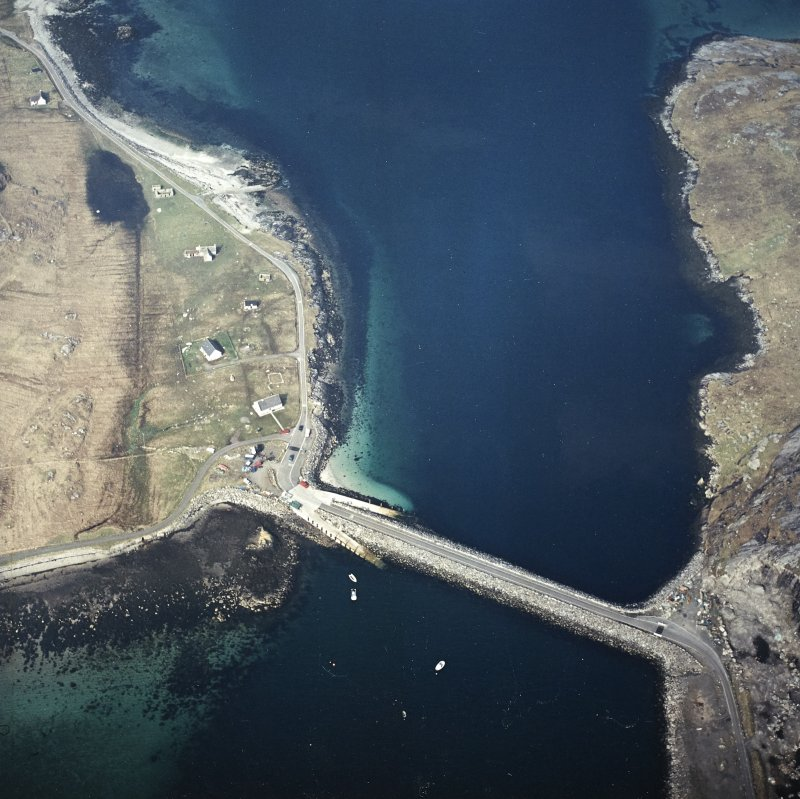 Oblique aerial view centred on the causeway and slipways with the crofting township adjacent, taken from the ESE.
