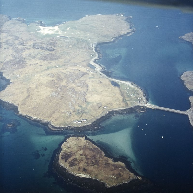 General oblique aerial view over the island of Vatersay with the causeway and fish traps in the foreground, taken from the ESE.