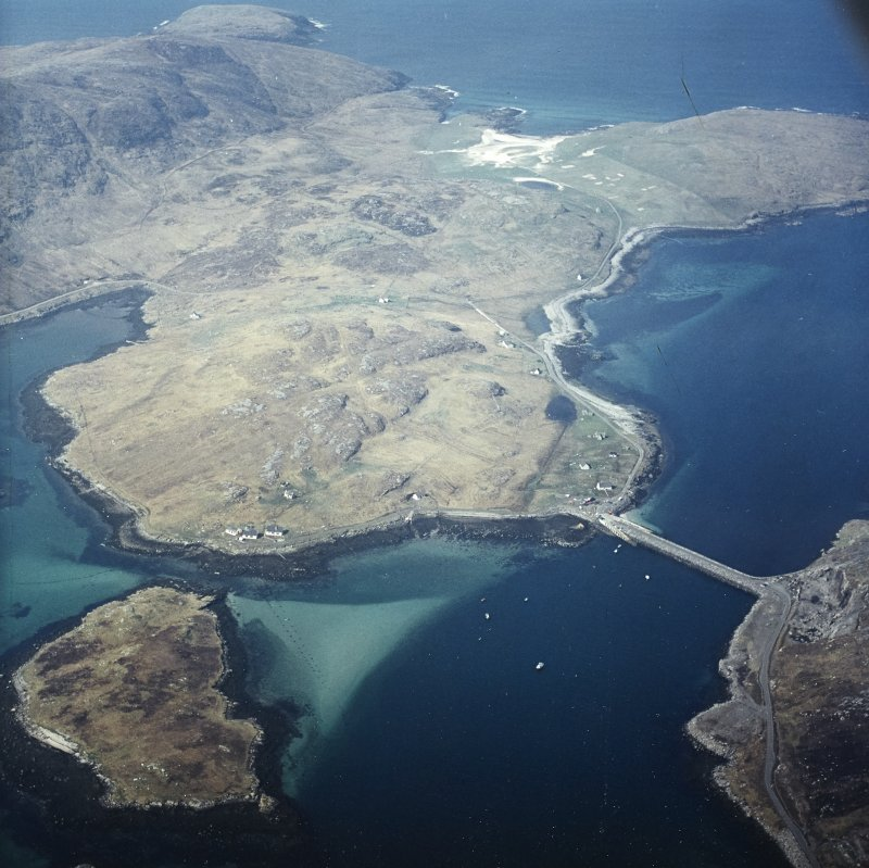General oblique aerial view over the island of Vatersay with the causeway and fish traps in the foreground, taken from the ENE.