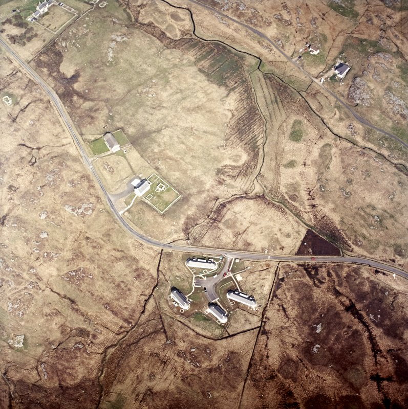 Oblique aerial view centred on the church, burial ground and manse with the houses adjacent, taken from the SE.