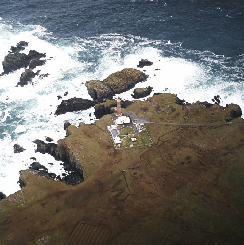 Oblique aerial view centred on the lighthouse with the remains of the enclosure adjacent, taken from the SW.