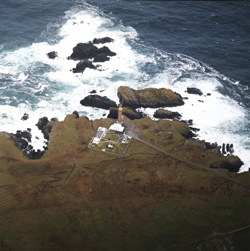 Oblique aerial view centred on the lighthouse with the remains of the enclosure adjacent, taken from the S.