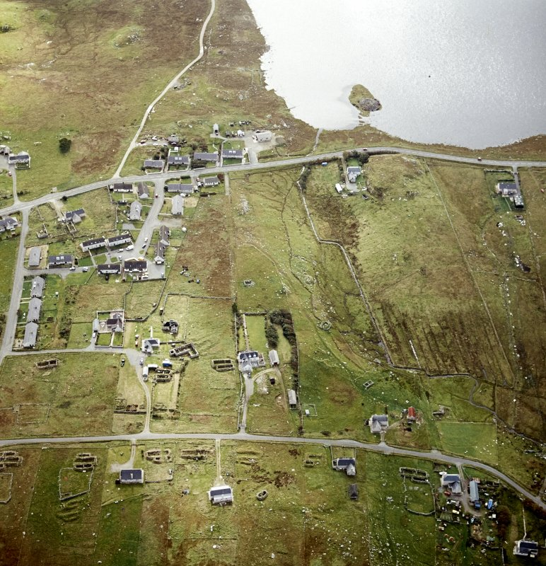 Oblique aerial view centred on remains of the horizontal mills with the remains of the corn-drying kiln, broch and possible crannog adjacent, taken from the N.