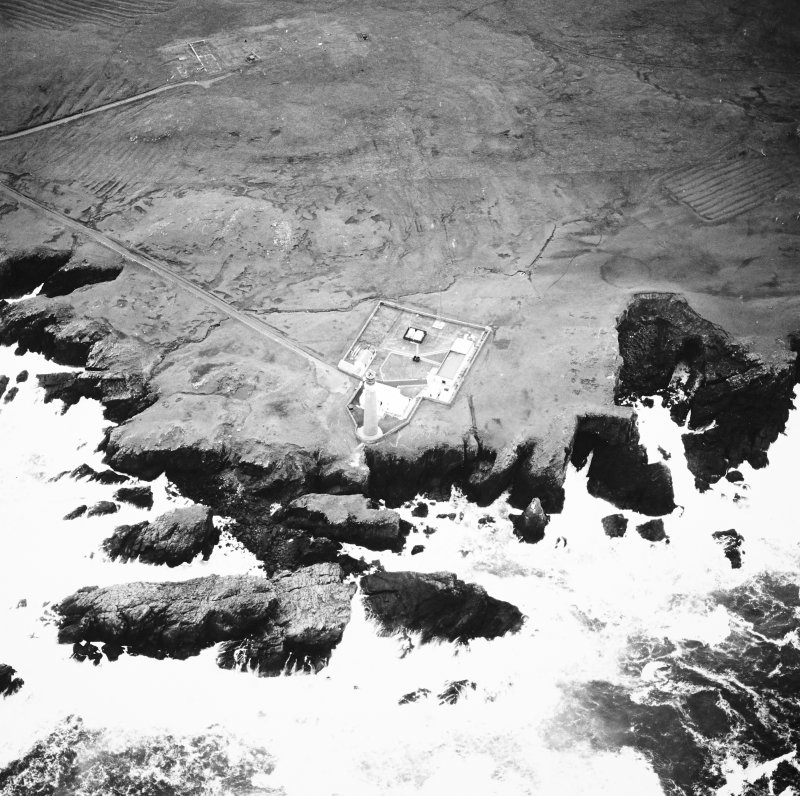 Oblique aerial view centred on the lighthouse with the remains of the enclosures adjacent, taken from the N.