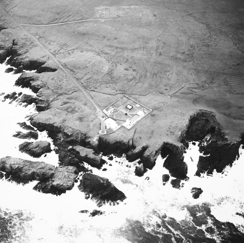 Oblique aerial view centred on the lighthouse with the remains of the enclosure adjacent, taken from the NNW.