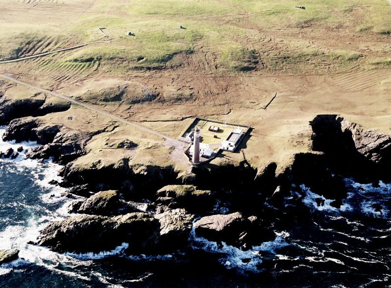 Oblique aerial view centred on the lighthouse with the enclosure and lazy beds adjacent, taken from the NNE.