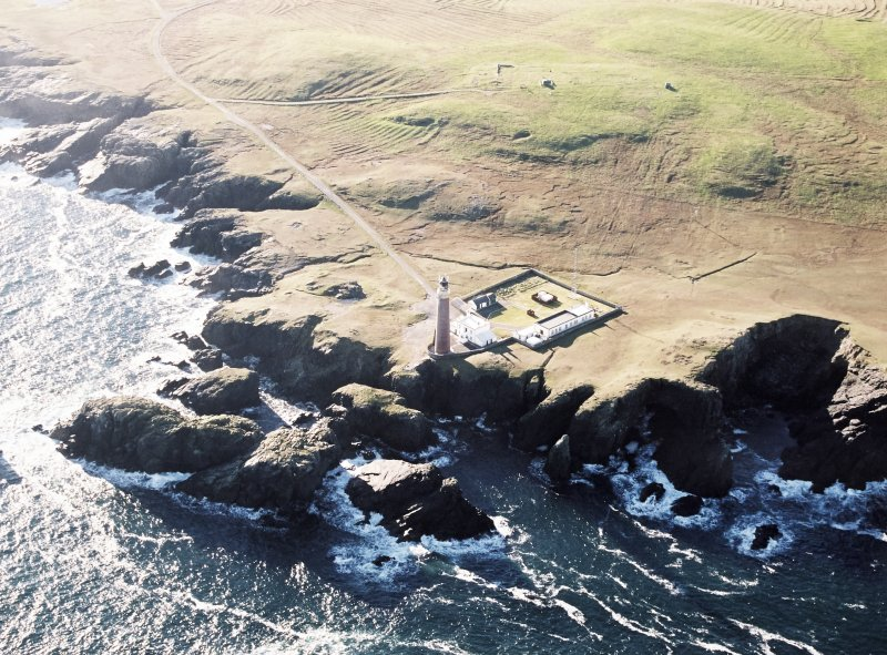 Oblique aerial view centred on the lighthouse with the enclosure and lazy beds adjacent, taken from the NNW.