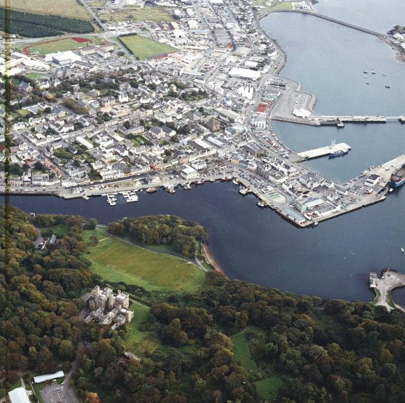 Oblique aerial view centred on the country house and college with Stornoway town centre and harbour adjacent, taken from the WNW.