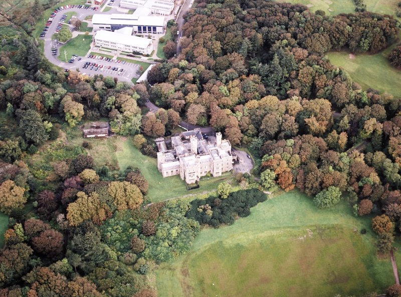 Oblique aerial view centred on the country house and college, taken from the SSE.