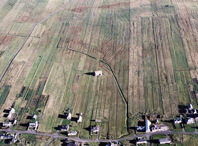 Oblique aerial view centred on the chapel with the township and lazy beds adjacent, taken from the SW.