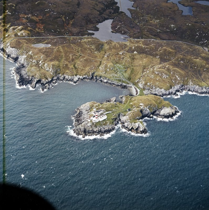Oblique aerial view centred on the lighthouse with the head-dyke, field system and lazy beds adjacent, taken from the ESE.