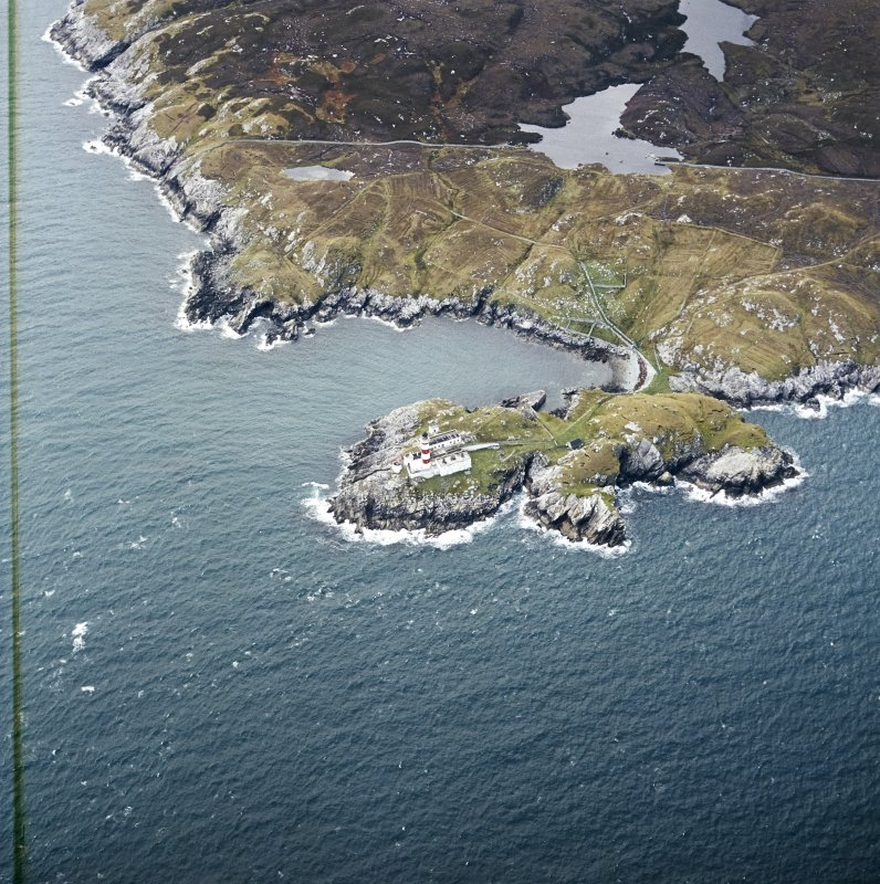 Oblique aerial view centred on the lighthouse with the head-dyke, field system and lazy beds adjacent, taken from the E.