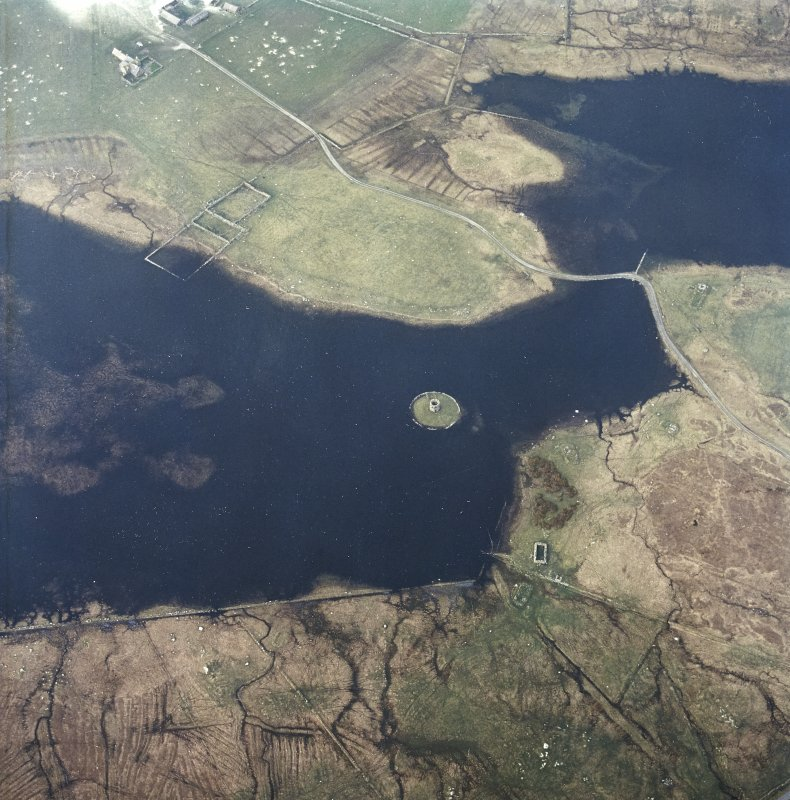 Oblique aerial view centred on the tower and remains of the dun with the remains of the township adjacent, taken from the S.
