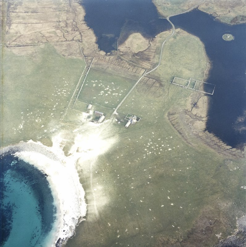Oblique aerial view centred on the farmstead and house with the tower and remains of the dun adjacent, taken from the WNW.