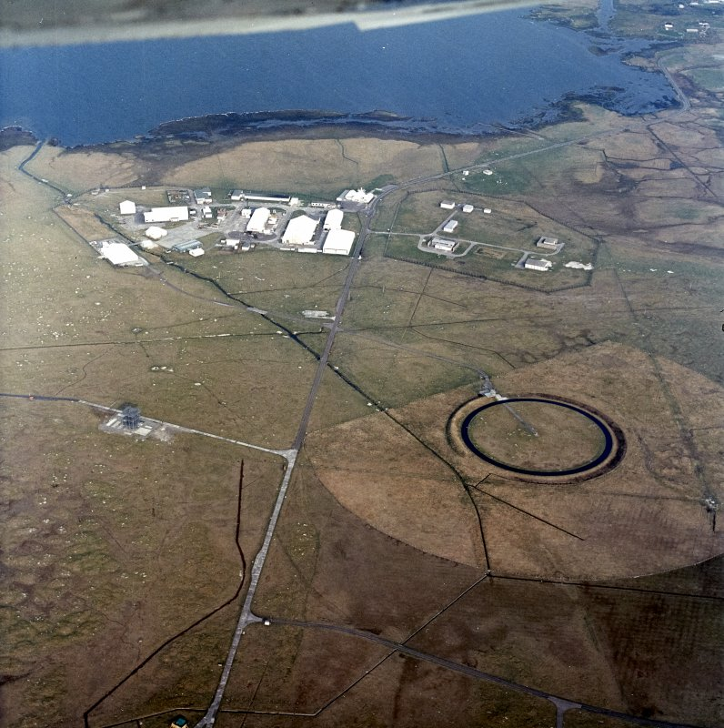 Oblique aerial view centred on the military installation, training area and buildings with the radio masts adjacent, taken from the W.