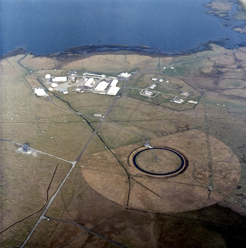 Oblique aerial view centred on the military installation, training area and buildings with the radio masts adjacent, taken from the WSW.