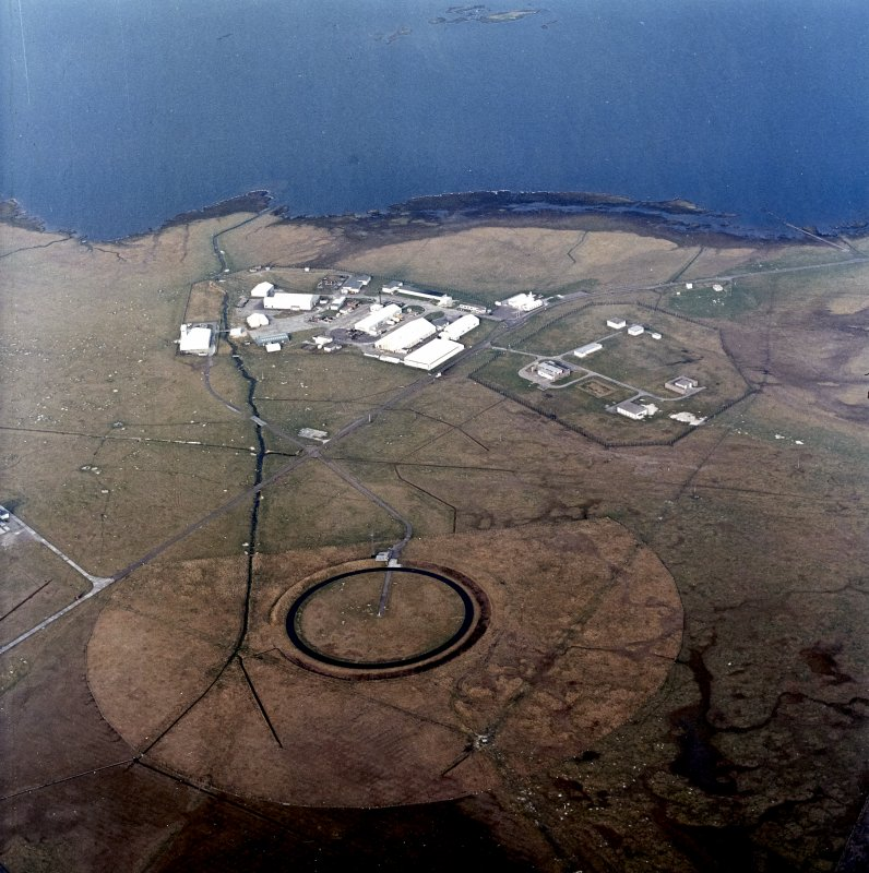 Oblique aerial view centred on the military installation, training area and buildings with the radio masts adjacent, taken from the SW.