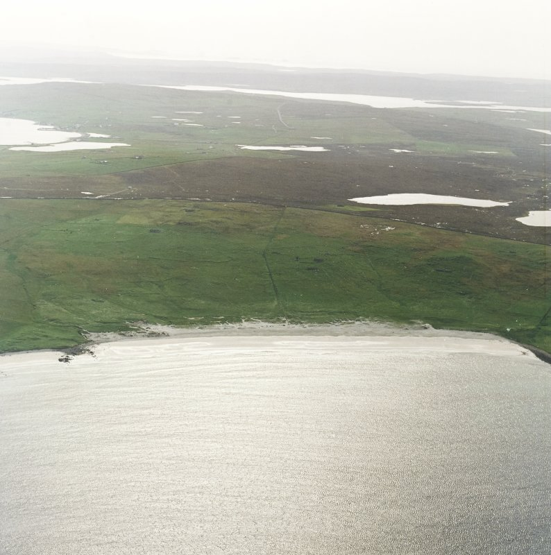 General oblique aerial view centred on the remains of the township, head-dyke and Viking settlement, taken from the NE.