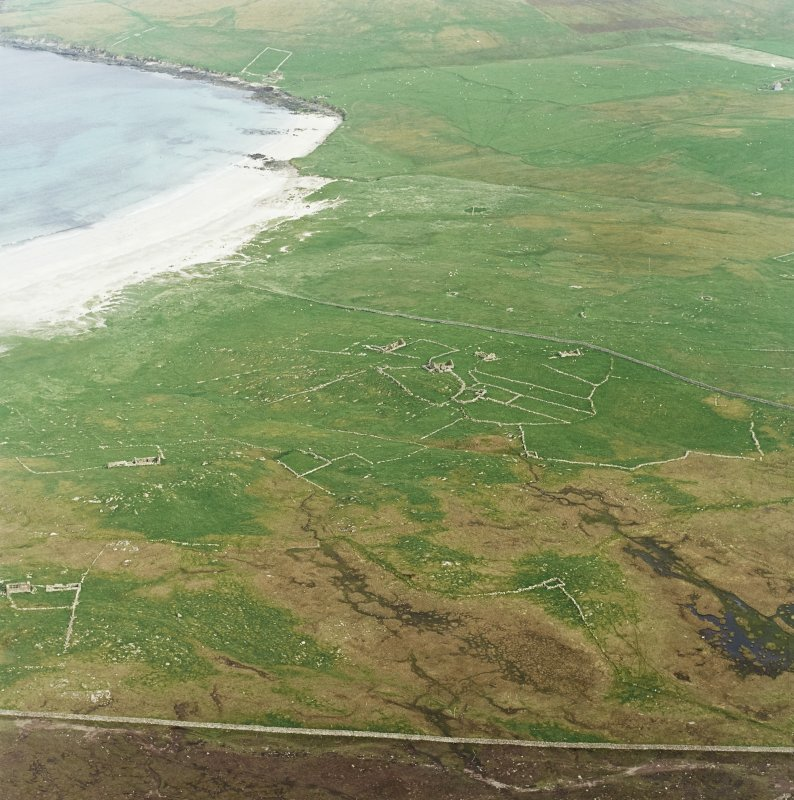 Oblique aerial view centred on the remains of the township and head-dyke, with the remains of the Viking settlement adjacent, taken from the NW.