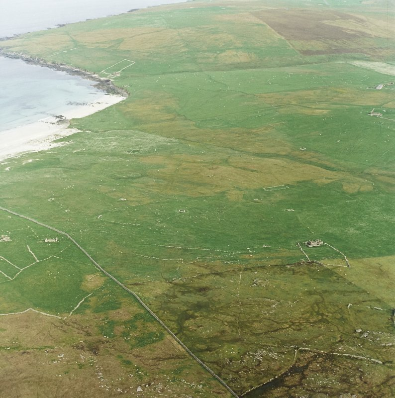 Oblique aerial view centred on the remains of the township and head-dyke, with the remains of the Viking settlement adjacent, taken from the WNW.
