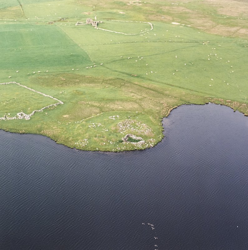Oblique aerial view centred on the remains of the broch with the remains of the buildings, burnt mound and croft buildings adjacent, taken from the SW.