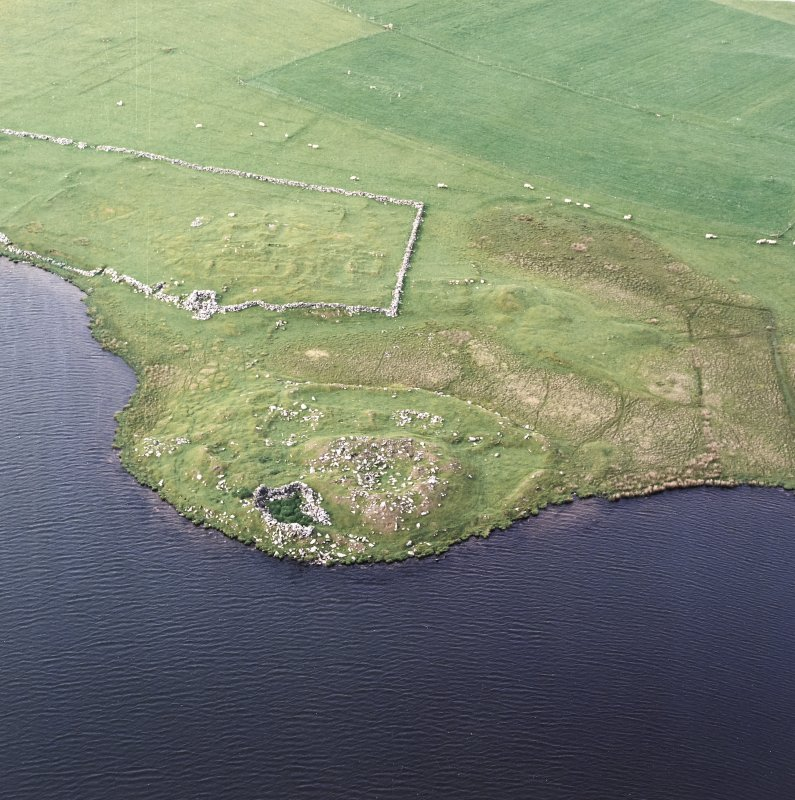 Oblique aerial view centred on the remains of the broch with the remains of the buildings and burnt mound adjacent, taken from the S.