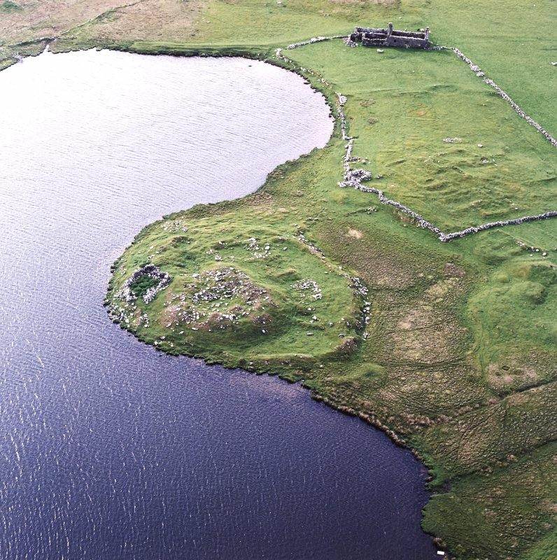Oblique aerial view centred on the remains of the broch with the remains of the buildings, burnt mound and croft buildings adjacent, taken from the ESE.