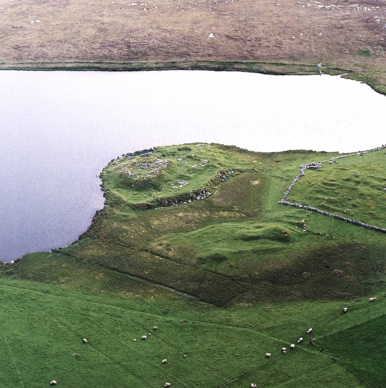 Oblique aerial view centred on the remains of the broch with the remains of the buildings and burnt mound adjacent, taken from the E.