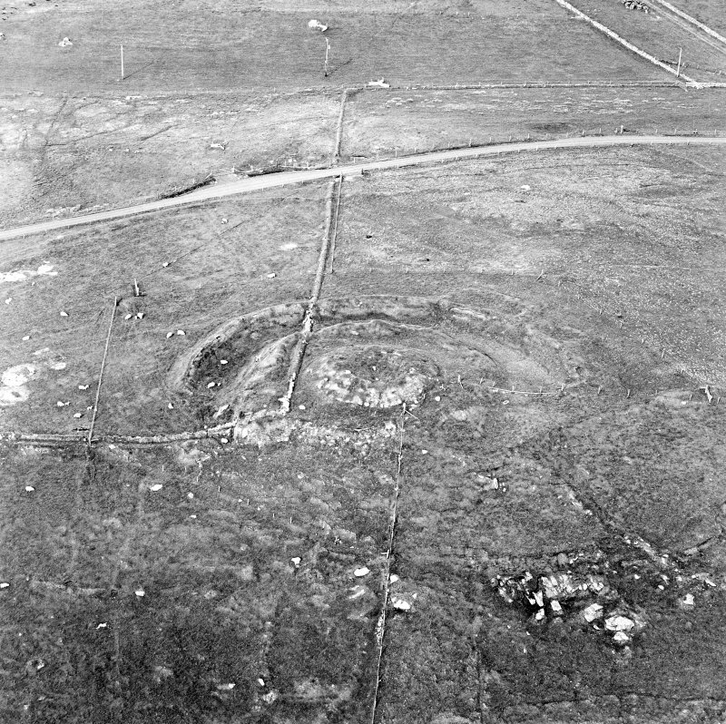 Oblique aerial view centred on the remains of the broch and field-system, taken from the SW.
