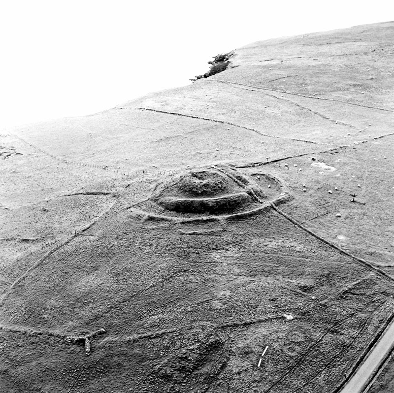 Oblique aerial view centred on the remains of the broch and field-system, taken from the ENE.