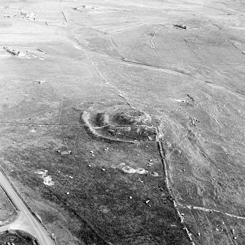 Oblique aerial view centred on the remains of the broch and field-system, taken from the NNW.