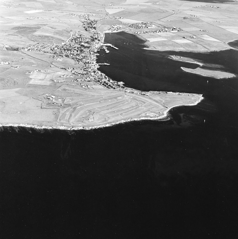 Oblique aerial view of Stromness, taken from the SSW.  Also visible are the First and Second World War Coastal batteries.