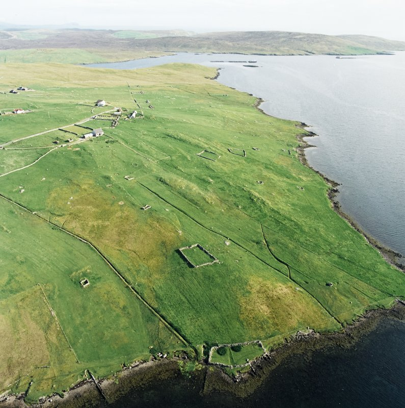Oblique aerial view centred on the remains of the township, chapel,  burial ground and head-dyke, taken from the NNW.