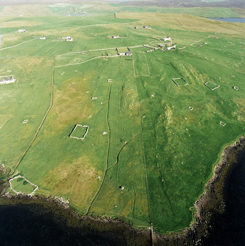 Oblique aerial view centred on the remains of the township, chapel,  burial ground and head-dyke with the remains of the burnt mound adjacent, taken from the NW.