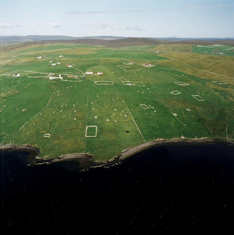 Oblique aerial view centred on the remains of the township, chapel,  burial ground and head-dyke, taken from the W.