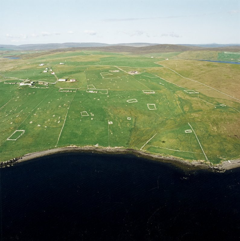 Oblique aerial view centred on the remains of the township, chapel,  burial ground and head-dyke, taken from the WSW.