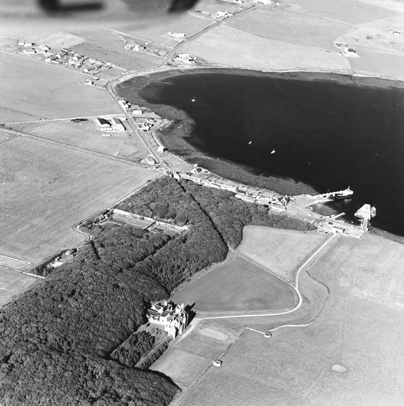 Oblique aerial view of Orkney, Shapinsay, Balfour Castle, Balfour village and harbour taken from the W.  Also visible is the former Balfour village gasometer