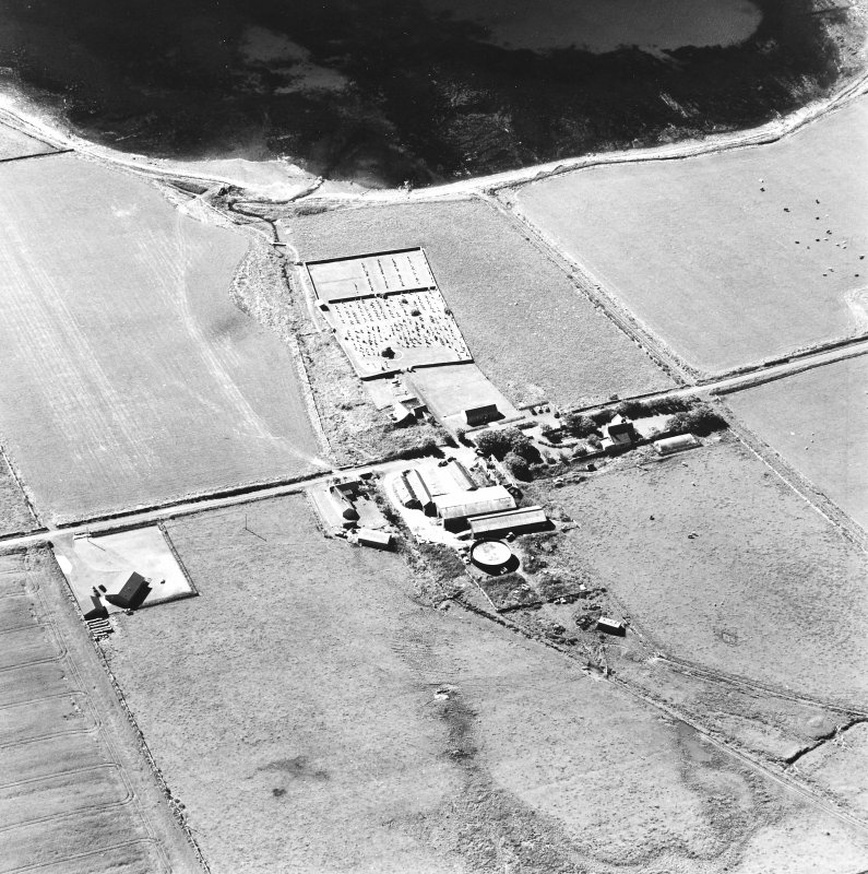 Oblique aerial view of Orphir, St Nicholas's Church, burial-ground and the Earl's Bu with mill, taken from the N. Also visible is the Bu of Orphir farmhouse and farmsteading.