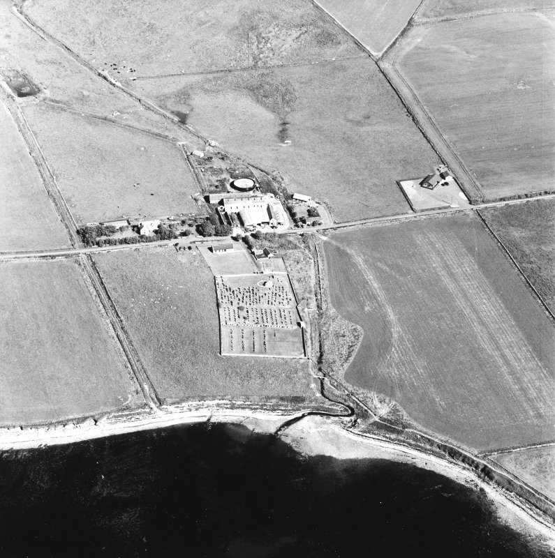 Oblique aerial view of Orphir, St Nicholas's Church, burial-ground and the Earl's Bu with mill, taken from the S. Also visible is the Bu of Orphir farmhouse and farmsteading.