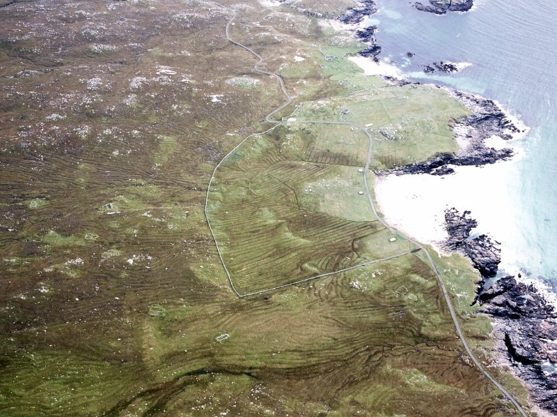 Oblique aerial view centred on the remains of the township and lazy beds with the remains of the radar station and possible nunnery adjacent, taken from the NNE.