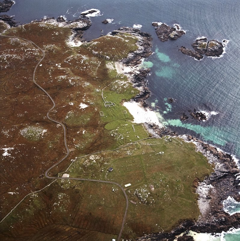 Oblique aerial view centred on the remains of the township and lazy beds with the remains of the radar station and possible nunnery adjacent, taken from the N.