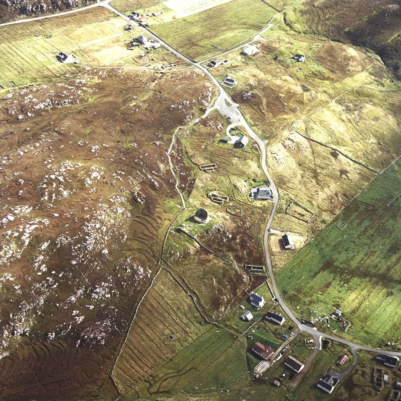 Oblique aerial view centred on the remains of the broch with the remains of the blackhouse and township adjacent, taken from the WNW.