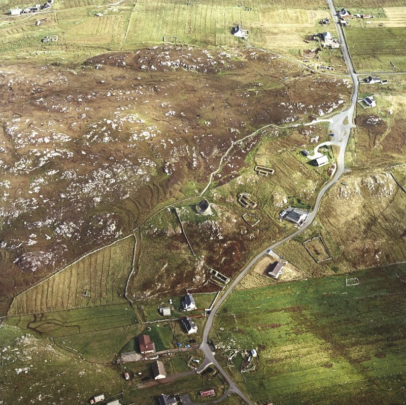 Oblique aerial view centred on the remains of the broch with the remains of the blackhouse and township adjacent, taken from the WSW.