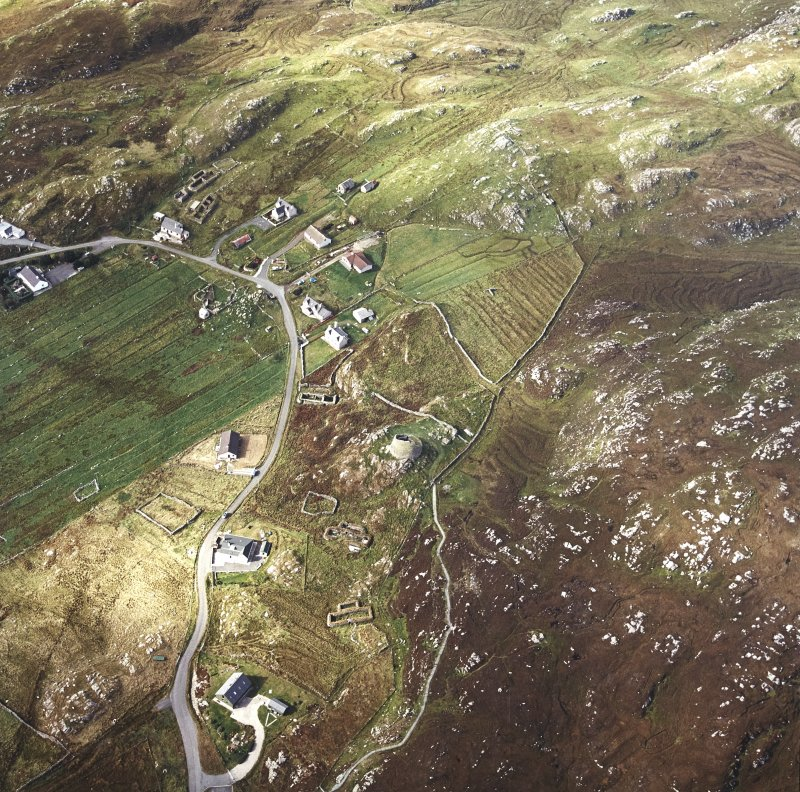 Oblique aerial view centred on the remains of the broch with the remains of the blackhouse and township adjacent, taken from the ESE.